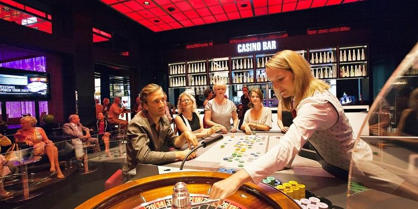 Vier Roulettespieler sitzen am Roulettetisch, der weibliche Croupier dreht die Roulettescheibe.