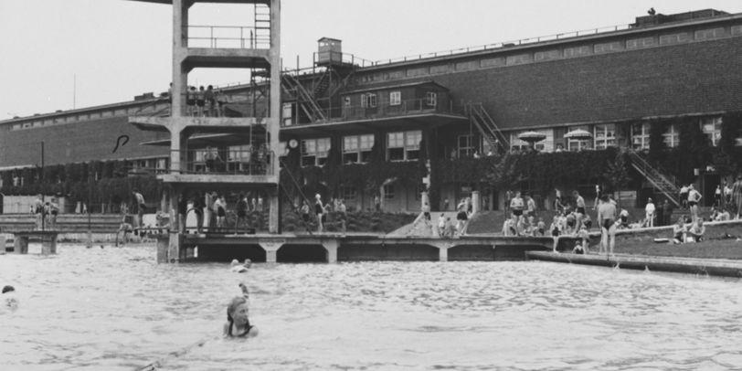 Der frontale Blick in schwarz-weiß auf ein Schwimmbecken, an dessen Beckenrand ein Schlauch liegt. Im Wasser schwimmen einige Menschen. Im Hintergrund steht eine Mauer. Außerdem steht ein Sprungturm auf einem Steg, der zum Wasser führt. Viele Menschen halten sich auf der gegenüberliegenden Wiese am Beckenrand auf.