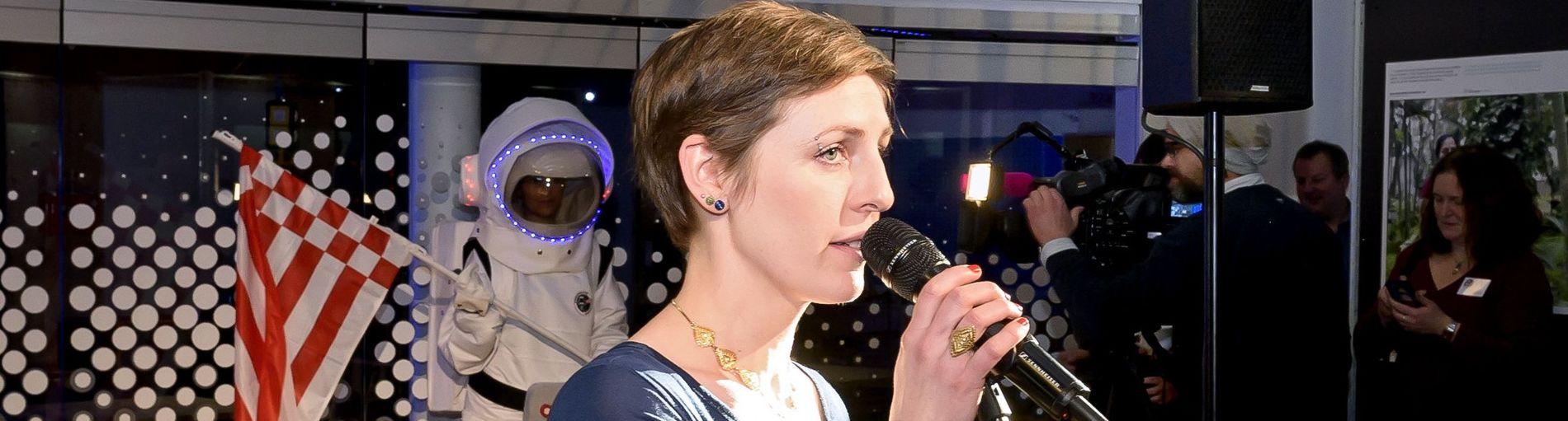 Eine Frau im blauen Kleid spricht in ein Mikrophon