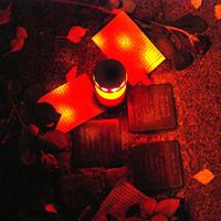 Brennende Kerze auf Stolpersteinen