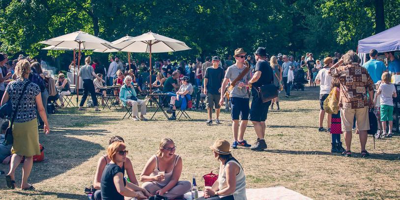 Eine Momentaufnahme auf dem sommerlichen Festival. Viele Menschen und im Vordergrund sitzen einige auf Pick-nick Decken.
