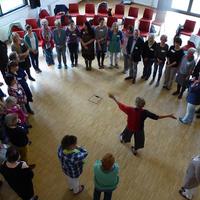 Menschen stehen in einem Kreis, in der Mitte gibt eine Frau Anweisungen; Quelle: Freiwilligen-Agentur Bremen