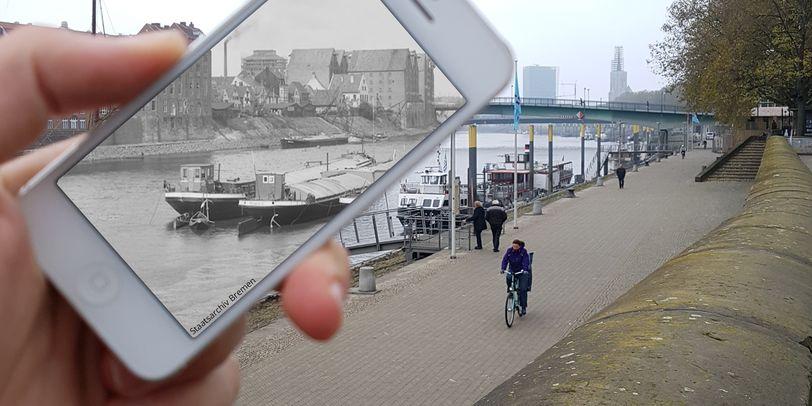 Zu sehen ist eine Hand, die ein weißes Smartphone festhält. Auf dem Bildschirm sind in schwarz-weiß 2 Schiffe zu erkennen, die auf einem Fluss liegen und Häuser, die auf der gegenüberliegenden Seite stehen. Der Rest des Bildes ist in Farbe und zeigt rechts eine Mauer und einen Steinweg am Ufer, auf dem Fußgänger und Radfahrer unterwegs sind.