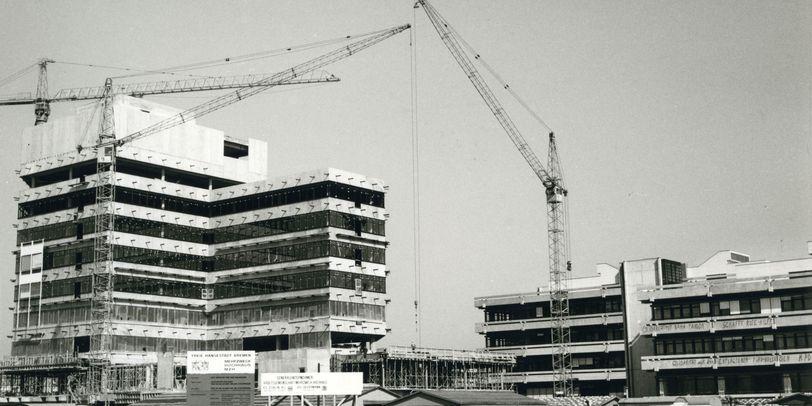 """Zu sehen ist ein großes Gebäude mit langen Glasfensterreihen auf jeder Etage. Rechts im Bild steht ein kleineres Gebäude. Außerdem sind 3 Kräne zu erkennen. Im vorderen Teil des Bildes sind Sandhaufen sowie Wohnanhänger zu sehen. Im unteren rechten Teil des Bildes ist der schwarze Schriftzug """"Staatsarchiv Bremen"""" zu lesen."""