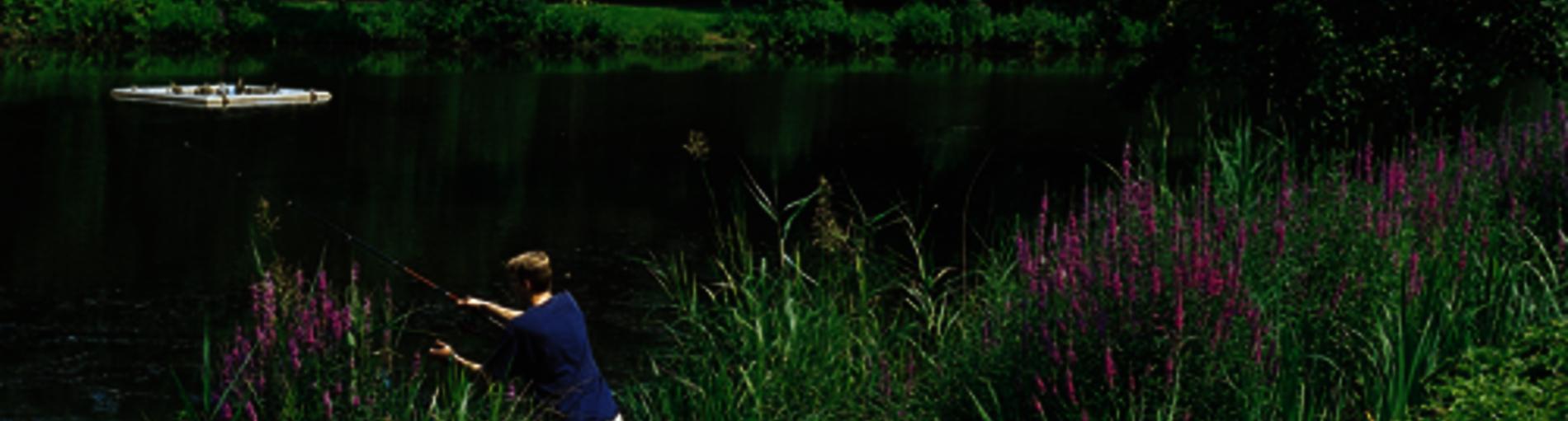 In der Grünanlage Vahr ein Mann mit Angel am See