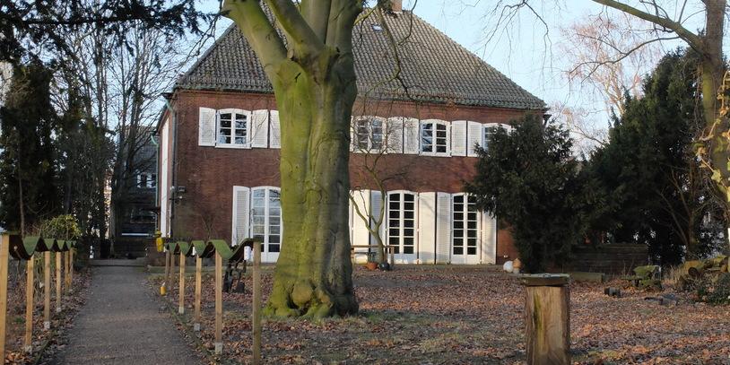 Backstein-Villa mit weißen Fensterläden, im Vordergrund ein herbstlicher Garten.