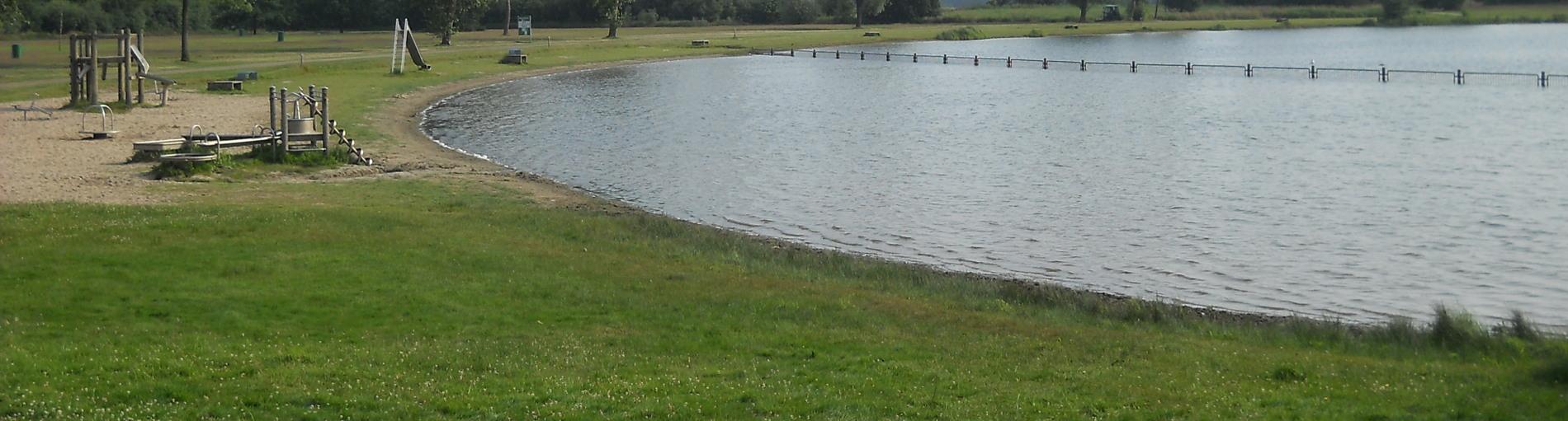 Eine grüne Wiese und zahlreiche Spielgeräte für Kinder liegen direkt am See
