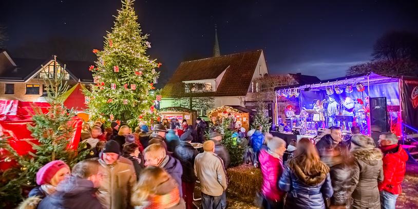 Weihnachtsmarkt in Ganderkesee. Im Vordergrund stehen Menschen und im Hintergrund ist ein großer Tannenbaum zu sehen sowie eine Band, die auf einer Bühne spielt.