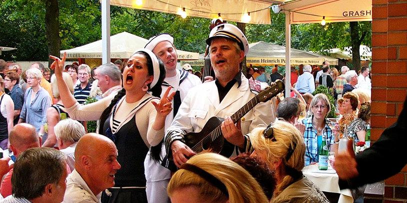 Eine Musikgruppe in Matrosenuniform singt inmitten von BesucherInnen des Weinfestes.