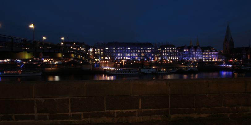 Blick über die Mauer auf die Weser am Abend mit beleuchteten Häusern