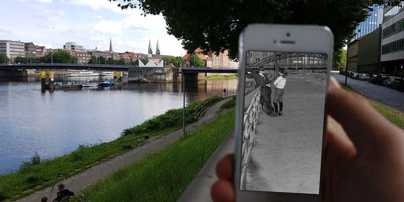 Zu sehen ist eine Hand, die ein weißes Smartphone in der Hand hält. Auf dessen Bildschirm ist ein Schwarz-Weiß-Bild zu sehen, das zwei Männer zeigt. Der eine von ihnen lehnt an einem Geländer. Der Rest des Bildes ist in Farbe. Links ist ein Fluss zu sehen, an dessen Ufer zwei Männer auf einer Bank sitzen. Im Hintergrund sieht man Häuser und eine Brücke.