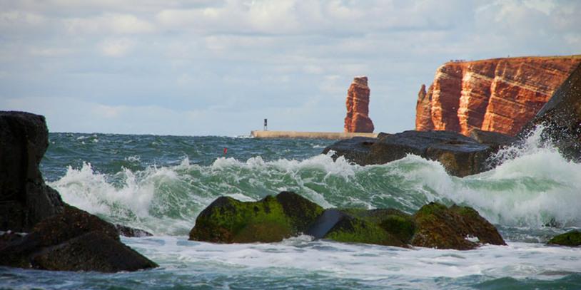 """Die Brandung an der westlichen Seite der Insel mit der """"Langen Anna"""" und den Klippen im Hintergrund. Quelle: Kurverwaltung Helgoland"""