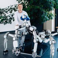 Ein Mann steht neben einem Roboter