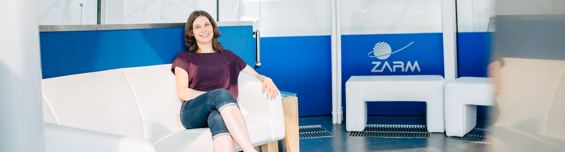 Eine Frau sitzt auf einem weißen Sofa