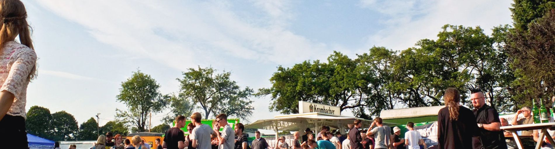 Die Festivalbesucher sitzen auf der Wiese und lauschen der Musik. Einige stehen und unterhalten sich.