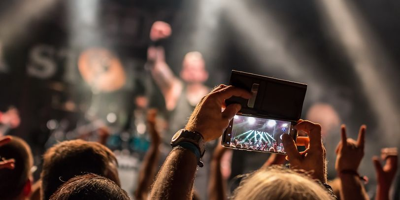 Die Bühne des Ziegelei Open Air im Hintergrund, nur verschwommen erkennbar. Im Vordergrund und scharf, das Publikum mit einem Smartphone auf dem der Auftritt gefilmt wird.