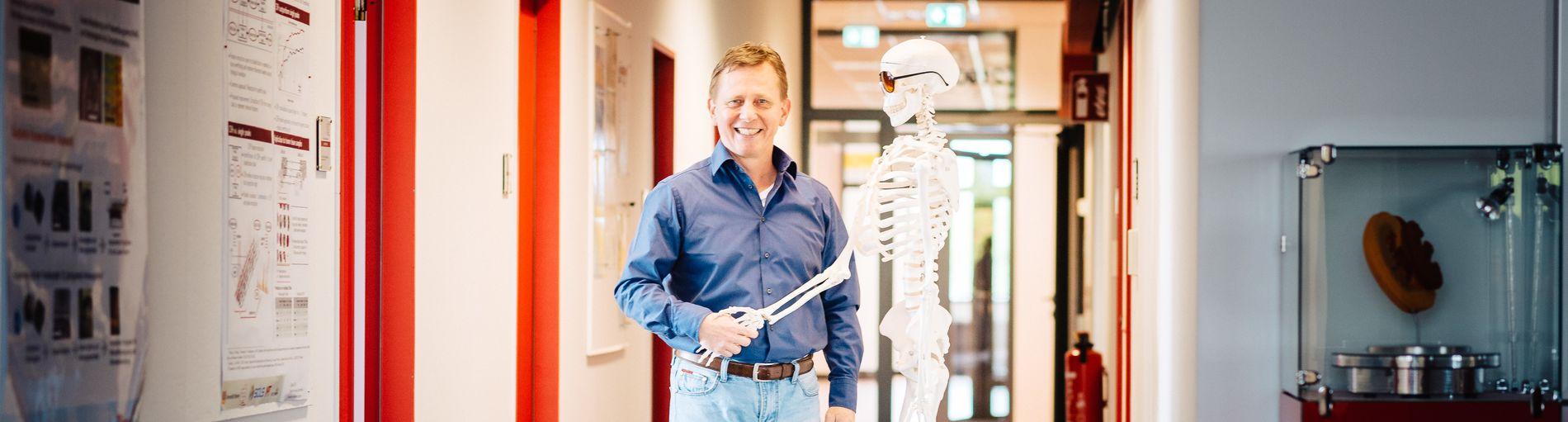 Ein Mann schüttelt einem Skelett die Hand und lächelt.