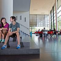 Junge Studenten sitzen auf einer Treppe im MZH der Uni Bremen.