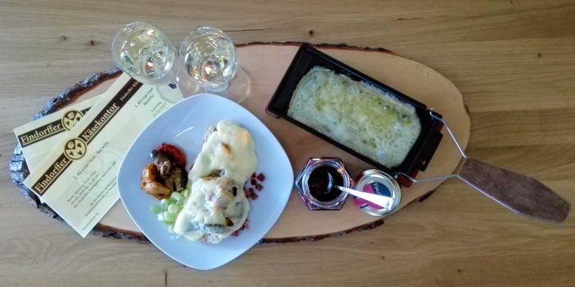 Gefüllte Raclettepfanne und Gutscheine auf Holzbrett