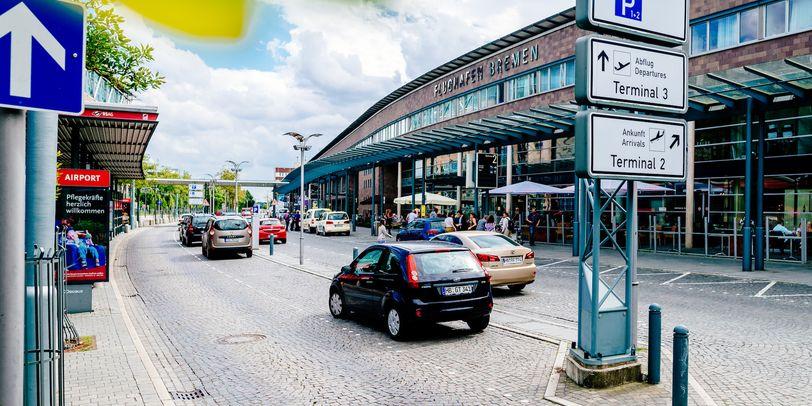 Außenansicht vom Flughafen Bremen mit parkenden Autos.
