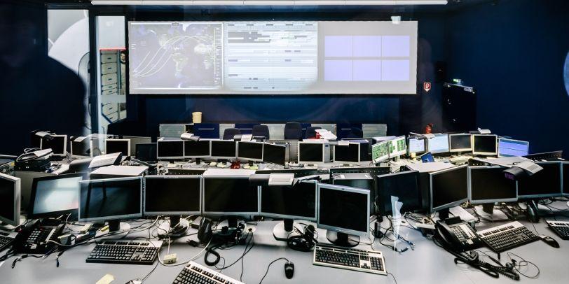 Viele Bildschirme, Tastaturen und Computer-Mäuse stehen aneinandergereiht auf zwei Tischen. Vor ihnen eine großes Whiteboard mit Bildübertragung.