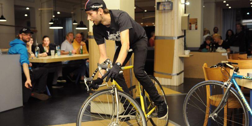 Mann fährt im Gebäude Fahrrad, hinter ihm sitzen Menschen am Tisch und sehen ihn an.