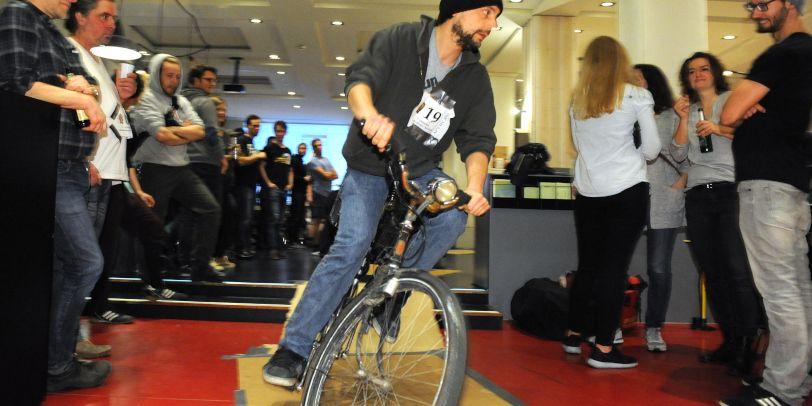 Mann fährt drinnen Fahrrad, Menschen schauen ihm dabei zu