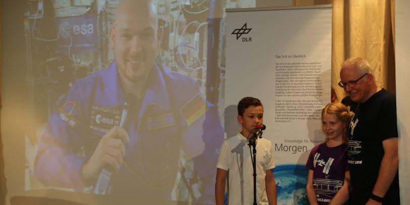 Zwei Kinder und ein Herr stehen mit einem Mikrophon auf der Bühne. Hinter ihnen ein Roll Up des DLR und eine große Leinwand mit Projektion des Astronauten Alexander Gerst.