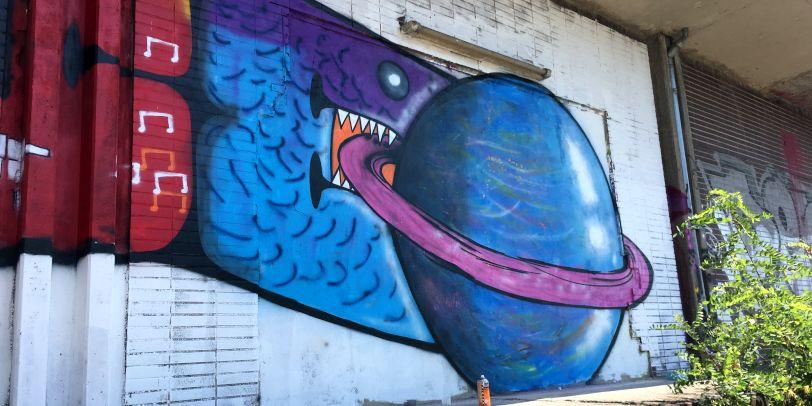 """Ein buntes """"E"""" und ein blaupinker Planet zieren als Graffiti die Wand."""