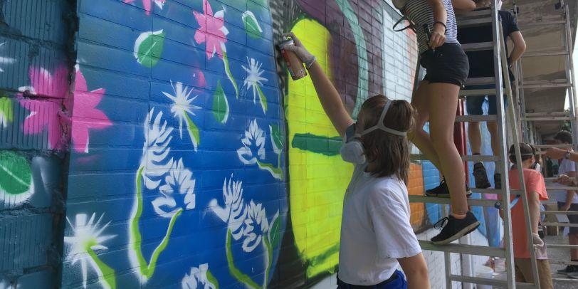 Ein Mädchen srpüht Graffiti an die Wand