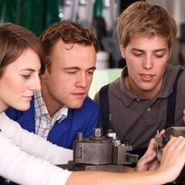 Ein Mädchen und ein Junge stehen mit ihrem Ausbilder an einer Maschine
