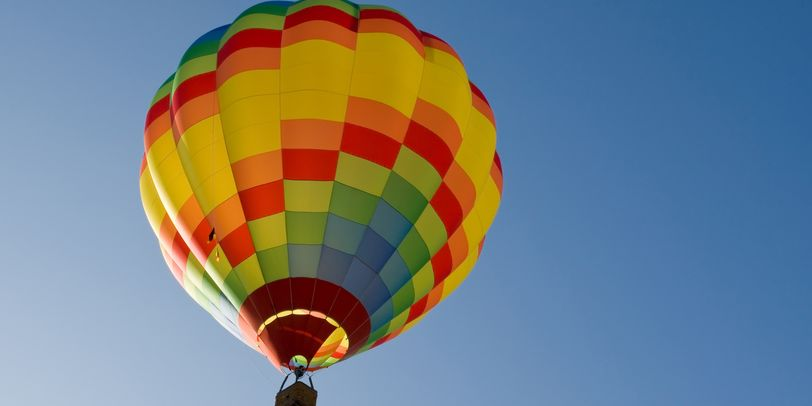 Ein bunter Heißluftballon steigt in den blauen Himmel.