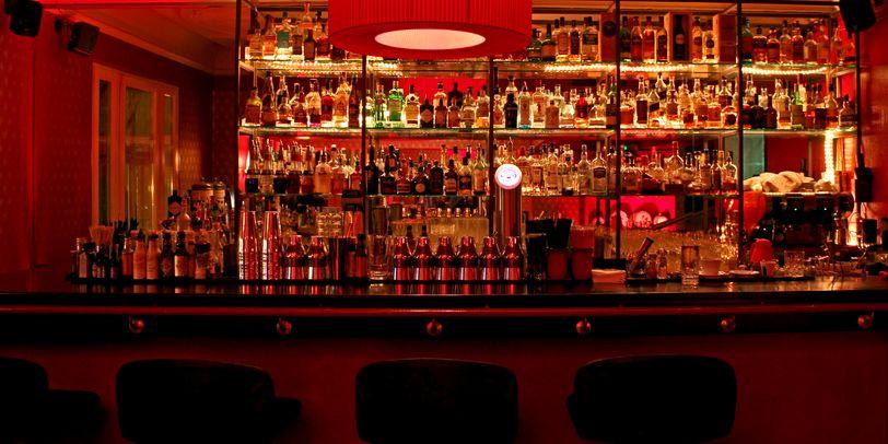 Eine Innenaufnahme der Lemonlounge in einem Rotorangenlicht seht ihr eine gut gefüllte Cocktailbar.