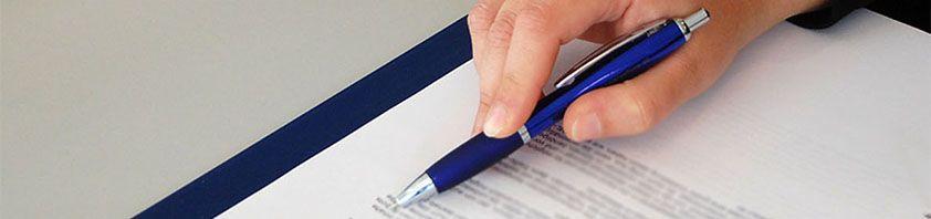 Eine Hand hält einen Kugelschreiber und fährt damit an einem Text entlang.