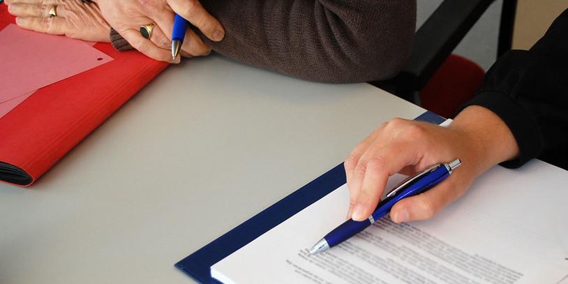 Zwei Personen schauen gemeinsam in ein Dokument