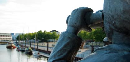 Statue mit Ferglas blickt auf den Hafen in Vegesack