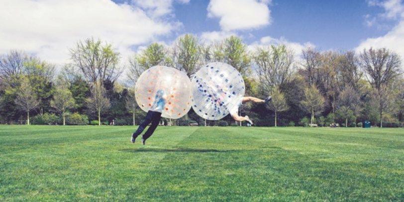 Zwei Menschen mit großen Bällen über dem Oberkörper springen aufeinander zu.