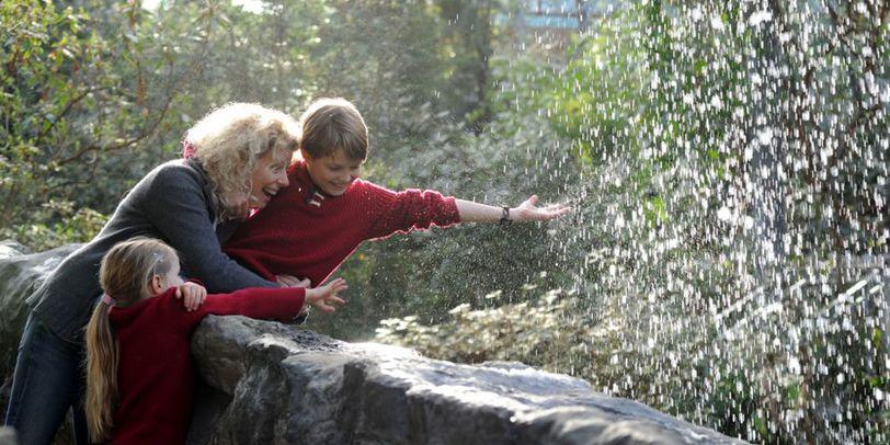 Eine Mutter mit zwei Kindern streckt die Hand nach einem Wasserfall aus.