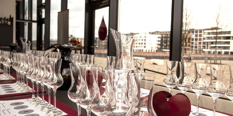 Auf dem Bild sind Gläser und Verkostungs-Bögen im Seminarraum zu sehen, im Hintergrund die Überseestadt