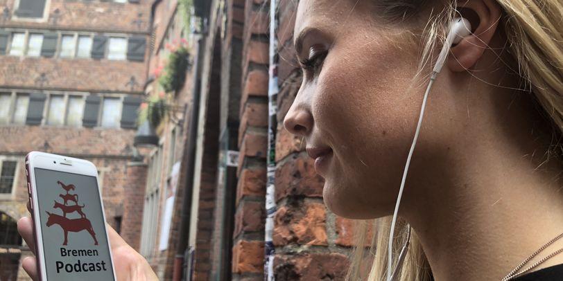 Eine junge Frau hält ihr Smartphone in der Hand. Auf dem Bildschirm ist das Logo des Bremen-Podcasts zu sehen.