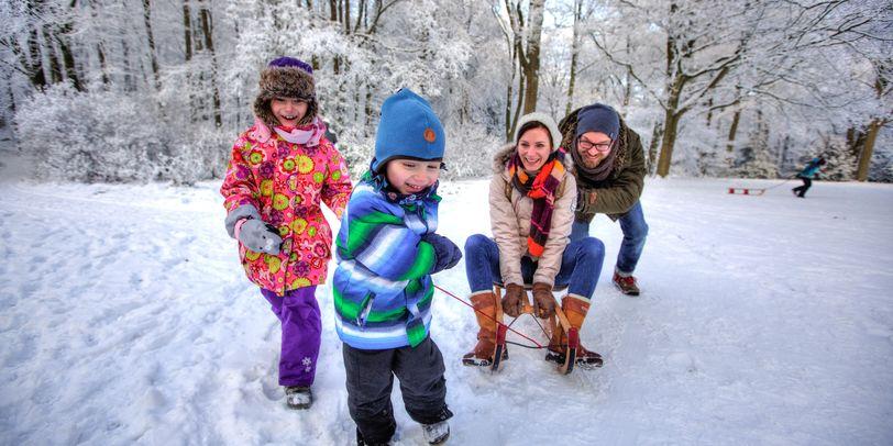 Eine Familie hat Spaß beim Schlittenfahren im Knoops Park