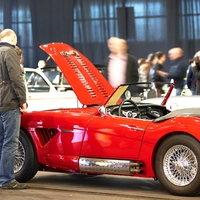 Beuscher der Bremen Classic Motorshow bestaunen einen roten Oldtimer.