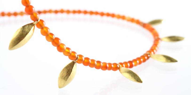 Eine Kette mit orangenen Perlen und goldenen Blättern.