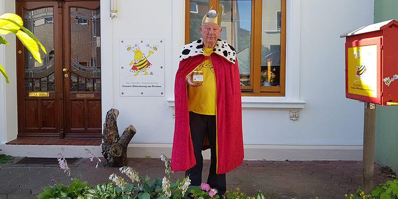 Heiner Lenz im Königskostüm und mit einem Glas Honig in der Hand vor seinem Haus in Walle.