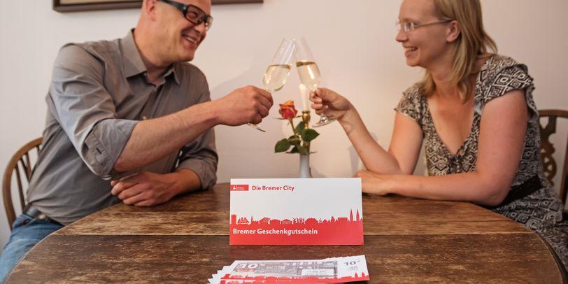 Im Hintergrund stoßen ein Mann und eine Frau mit Sekt an, vor ihnen liegt der Bremer Geschenkgutschein auf dem Tisch.