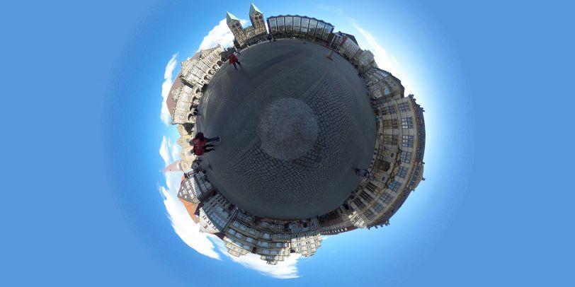 Eine runde Kugel, die Kopfsteinpflaster sowie Gebäude zeigt. Sie ist umgeben von blauem Himmel.