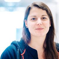 Ein Frau schaut in die Kamera, im Hintergrund ein Büroflur; Quelle WFB/Jonas Ginter