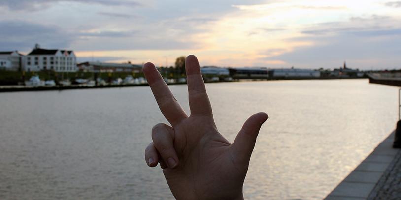 Eine Hand zeigt drei Finger, im Hintergrund die Weser