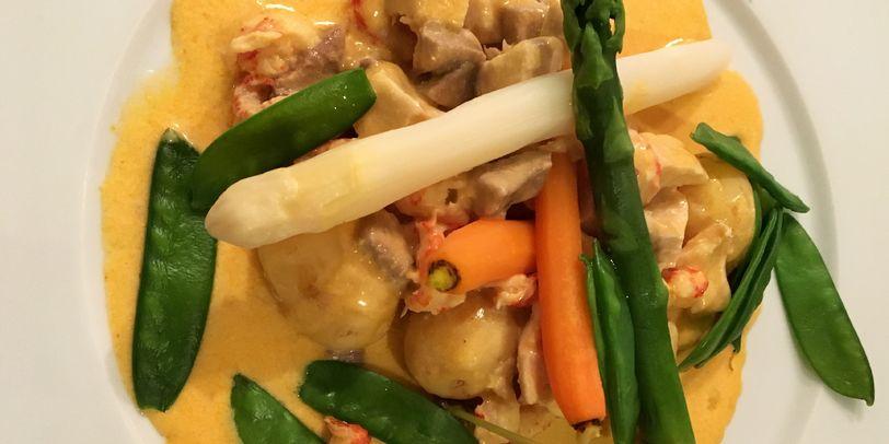 Das traditionelle Bremer Kükenragout mit Spargel, Karotten und Erbsenschoten auf einem weißen Teller angerichtet.