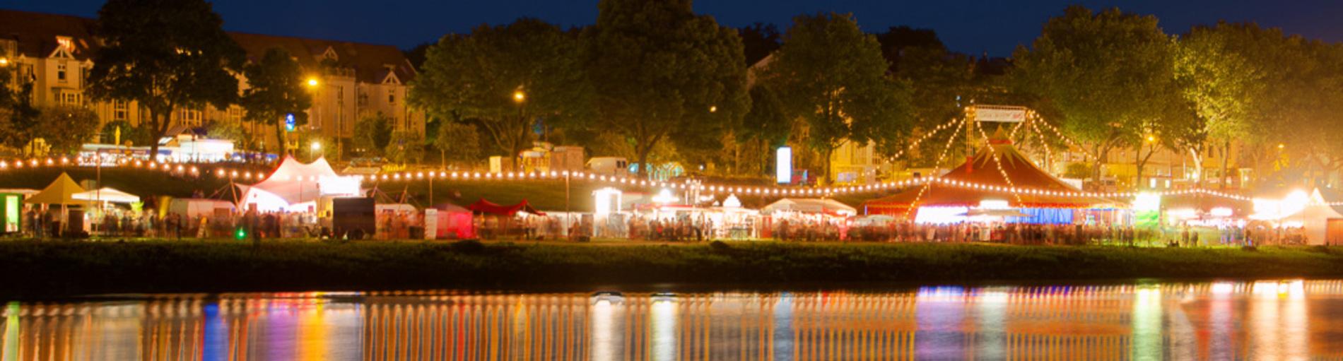 Blick auf festlich beleuchtete Festzelte zur Breminale an der Weser